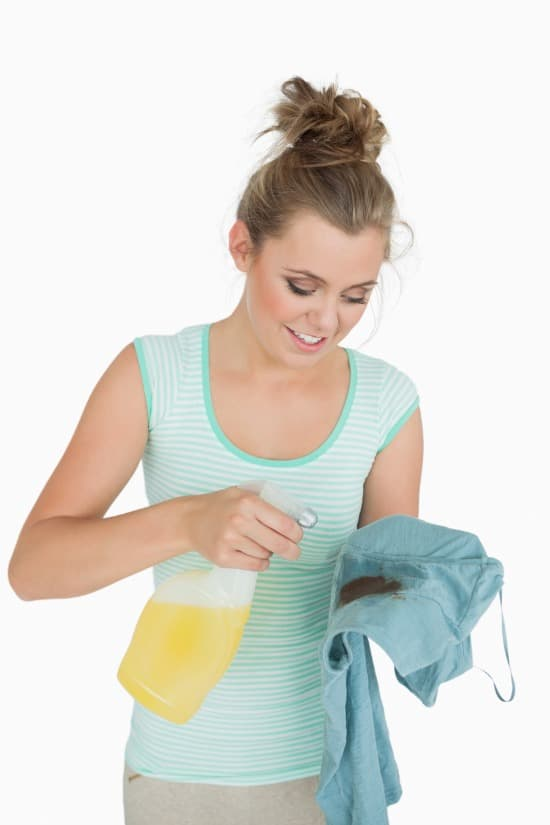 spraying enzyme cleaner on your cloth